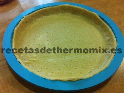 Forrado del molde con masa quebrada, es el primer paso de la receta de tarta de frutos secos.